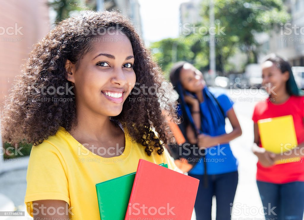 Laughing caribbean student in the city with friends stock photo