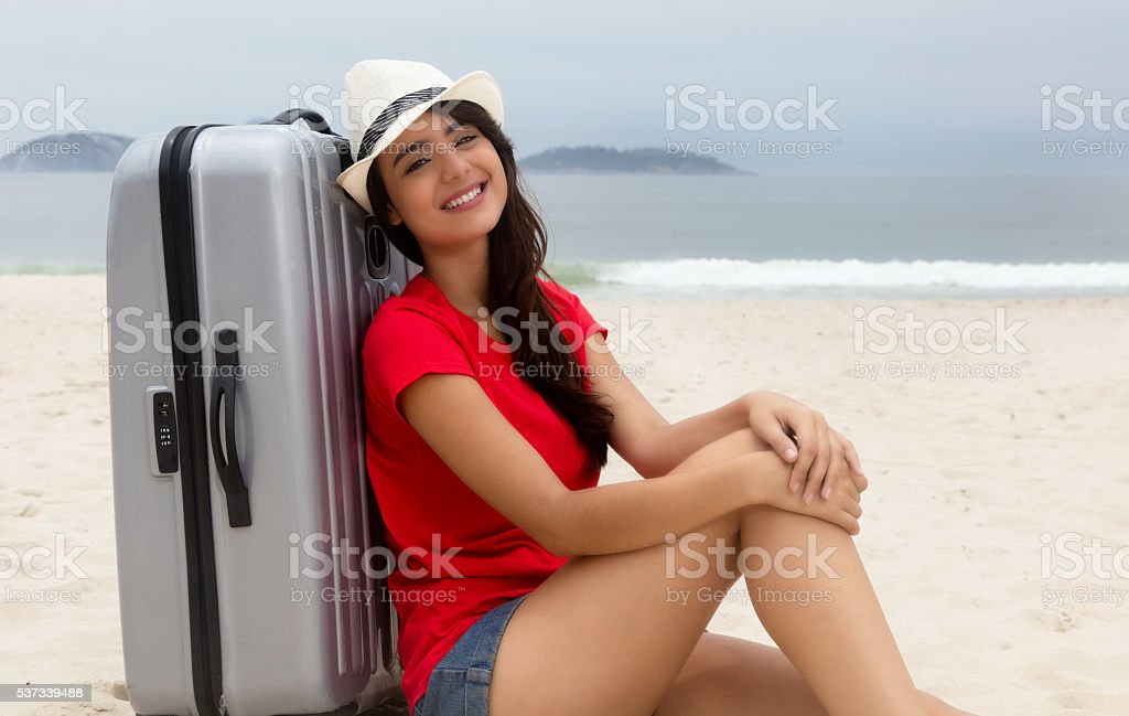 Laughing caucasian female tourist with suitcase at beach stock photo