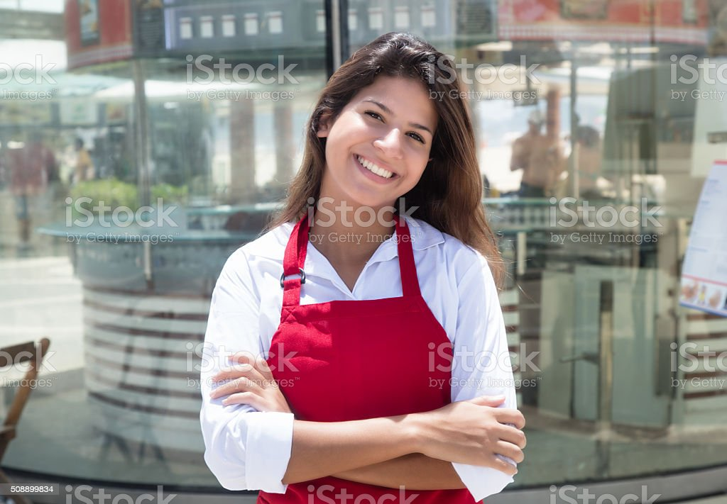 Laughing caucasian waitress in front of the restaurant stock photo