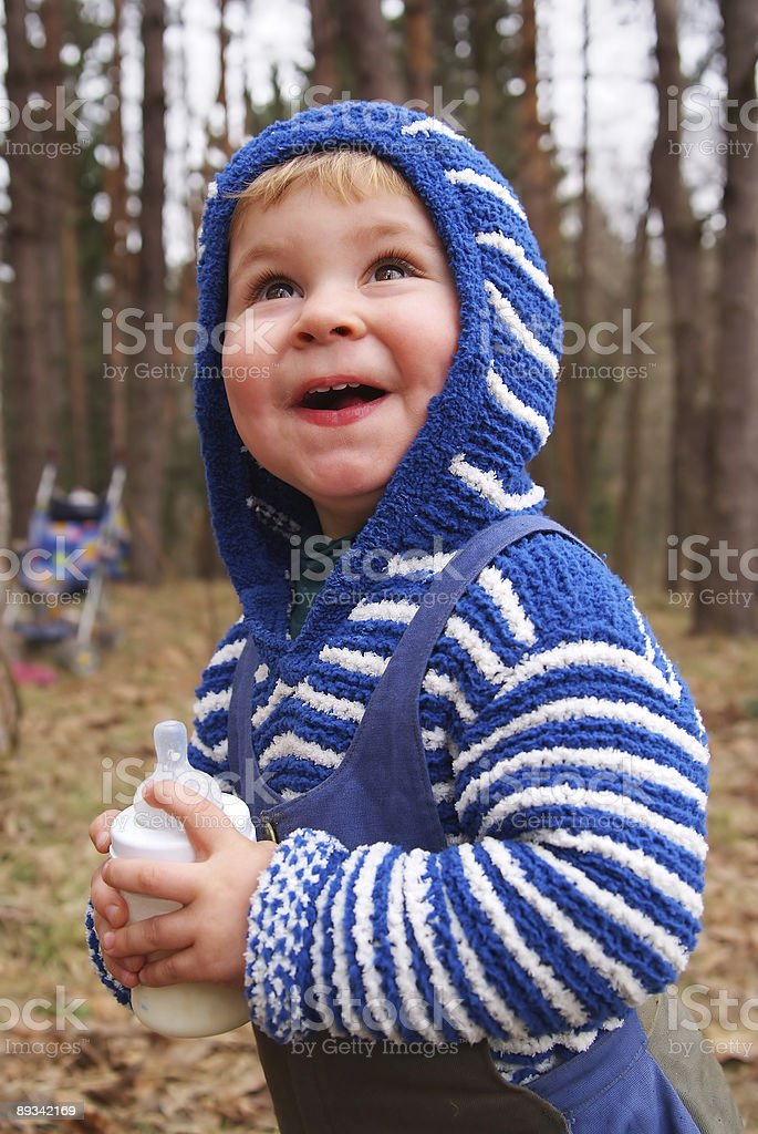 laughing child with small bottle of milk in hands royalty-free stock photo