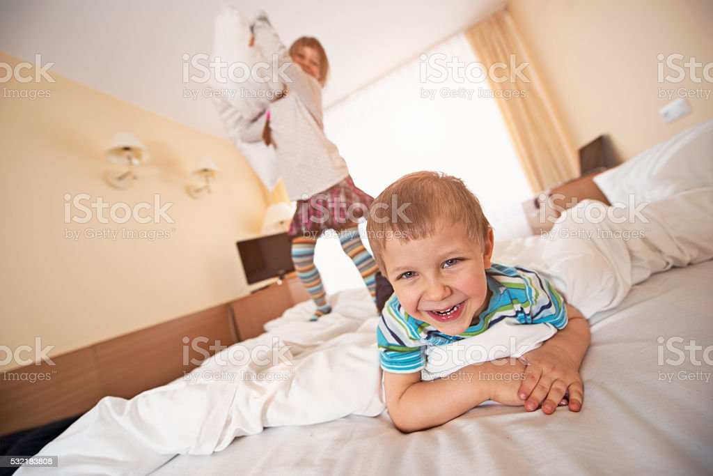 Laughing children having a pillow fight stock photo
