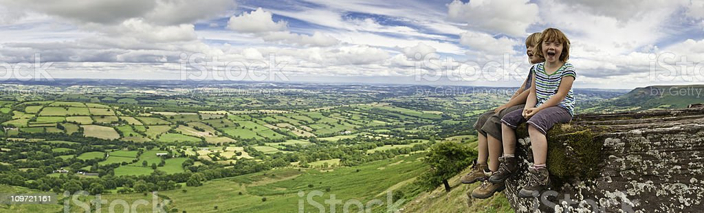 Laughing children on mountain top overlooking green summer landscape panorama royalty-free stock photo