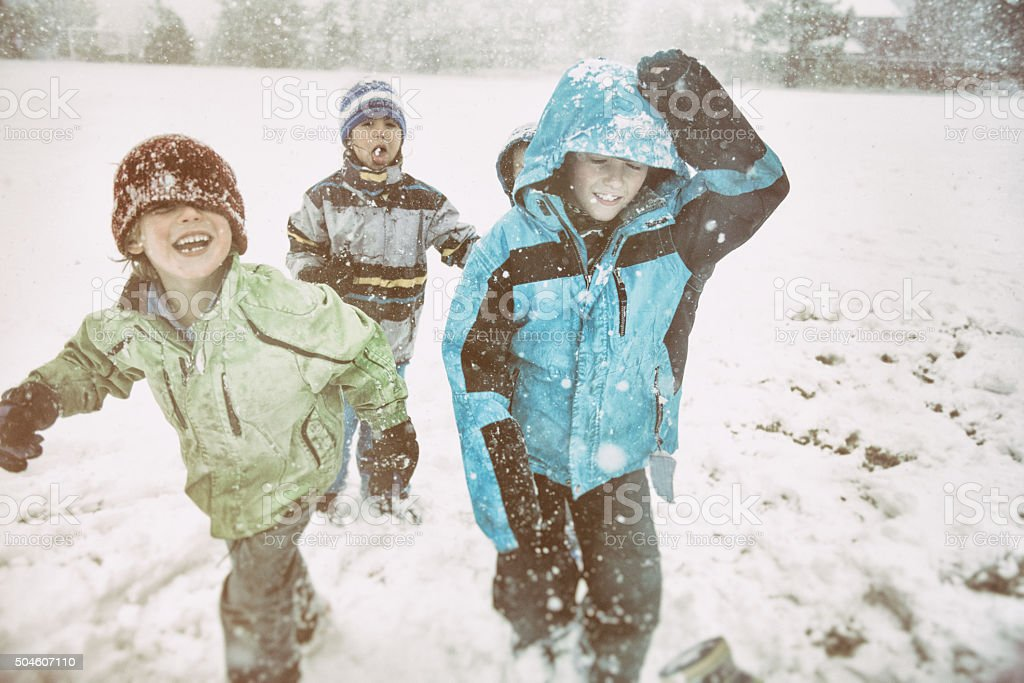 Laughing children playing in snow storm on a school field stock photo
