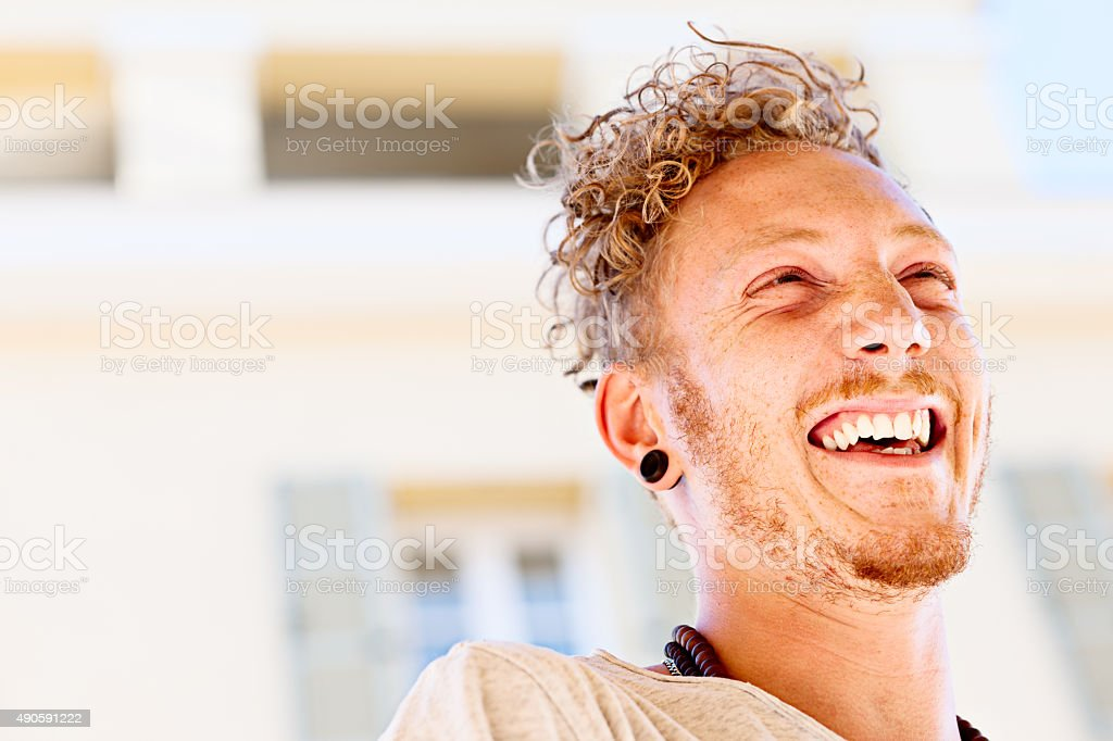 Laughing cool young man outdoors stock photo