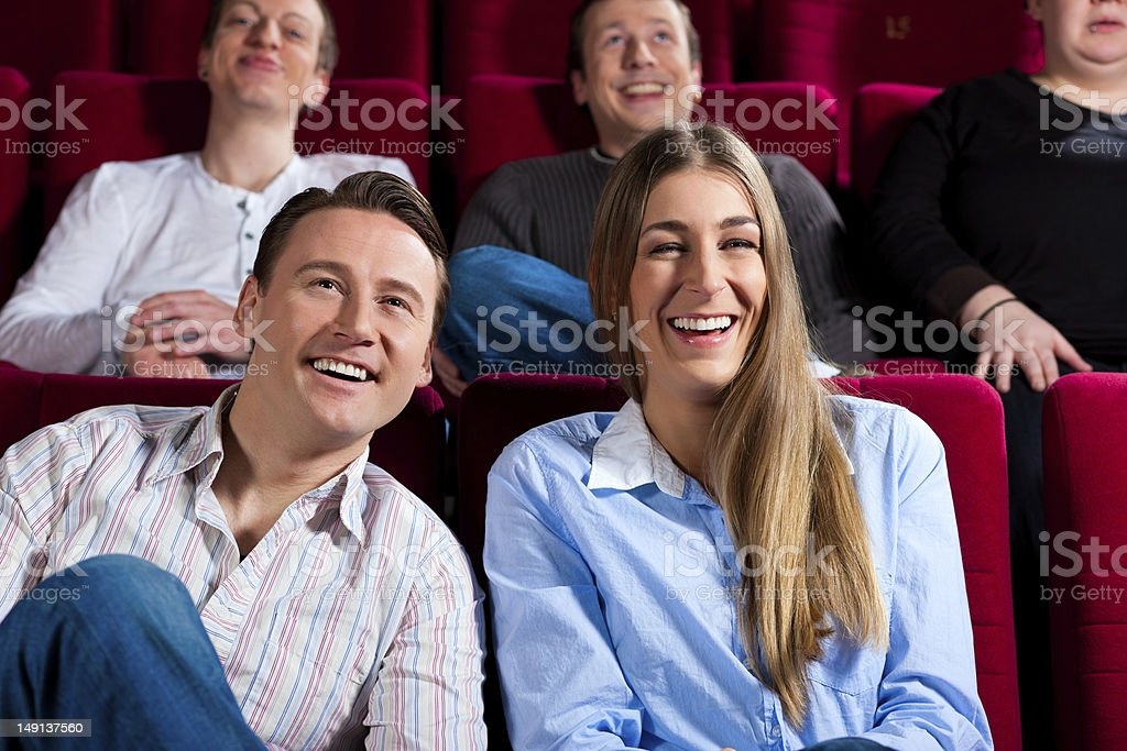 Laughing couple amongst other people in a movie theater royalty-free stock photo