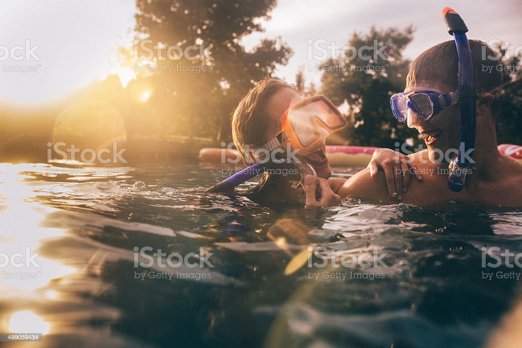 Laughing couple in pool wearing snorkelling gear with lens flare stock photo