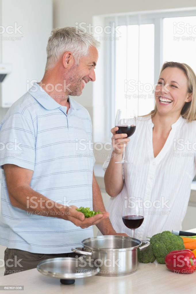 Laughing couple making dinner together stock photo