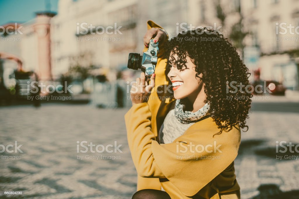 Laughing curly woman with retro camera stock photo