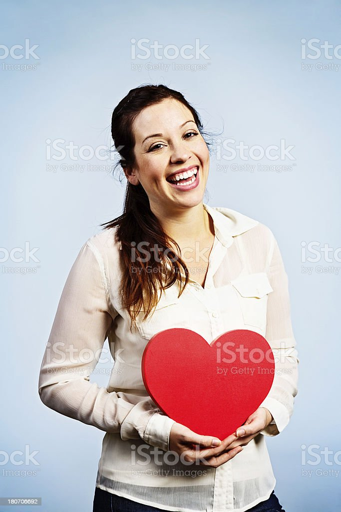 Laughing, dimpled brunette holds large red Valentne heart royalty-free stock photo