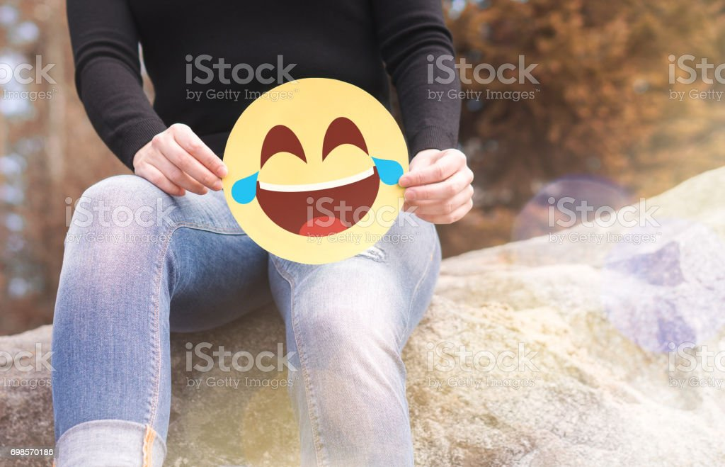 Laughing emoticon with tears of joy. Woman having fun outside and holding a cheerful printed paper smiley face. Happy   communication and smiley icon on cardboard. Happiness, joy and expression concept. stock photo