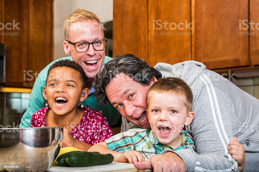 Laughing Family with Gay Dads in Kitchen stock photo