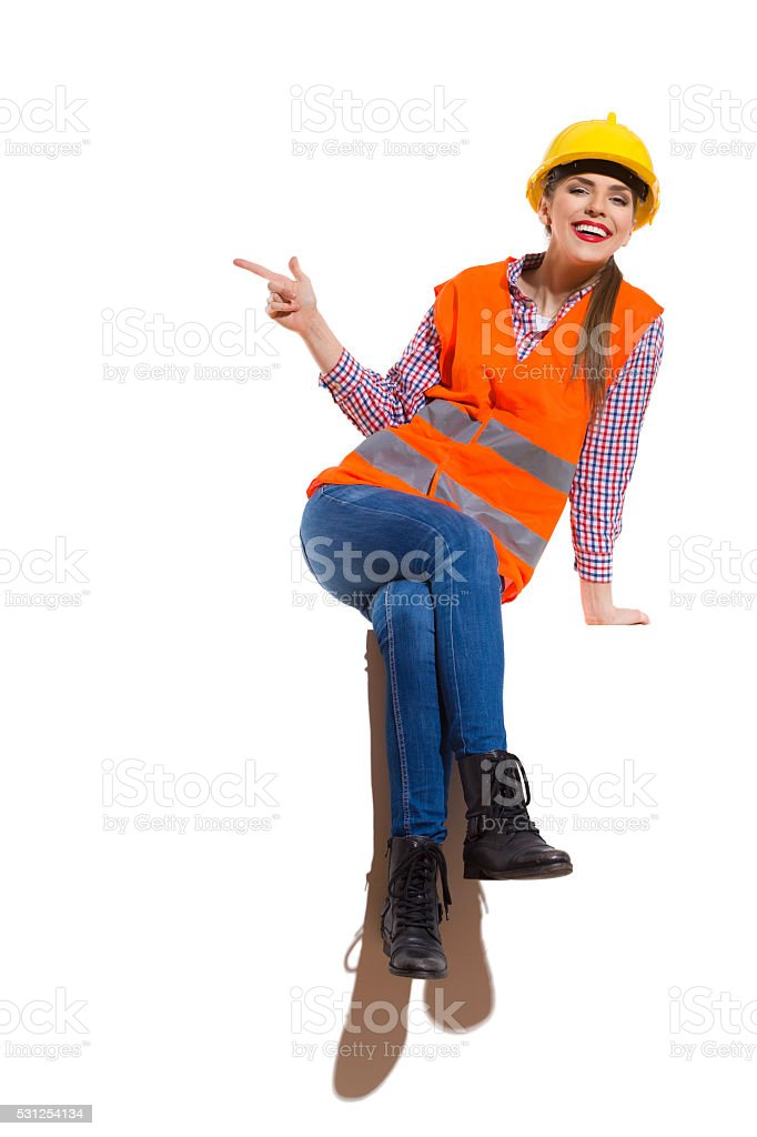Laughing Female Construction Worker Sitting And Pointing stock photo
