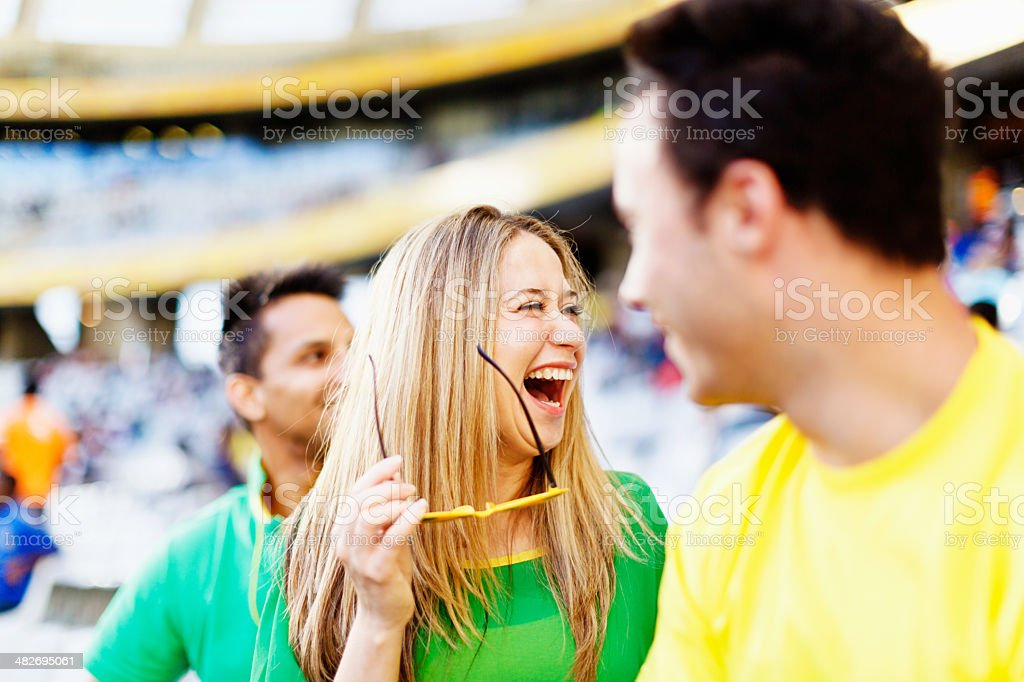 Laughing female football fan sees something funny royalty-free stock photo
