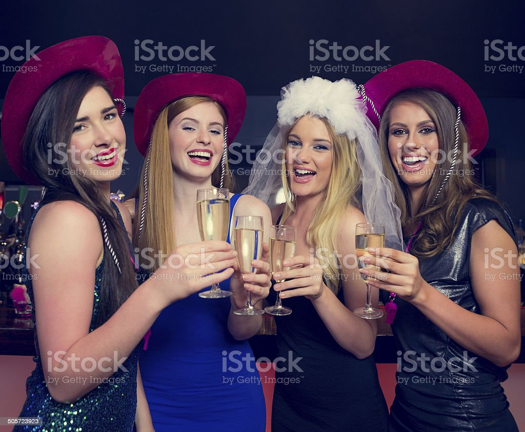 Laughing friends clinking champagne glasses at a hen night stock photo