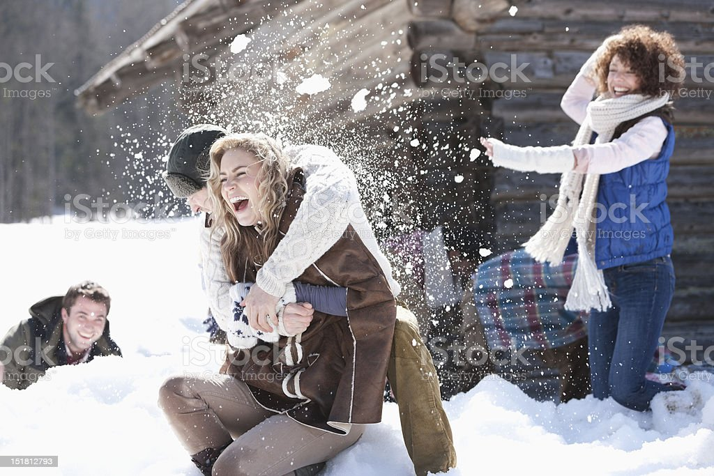 Laughing friends enjoying snowball fight stock photo