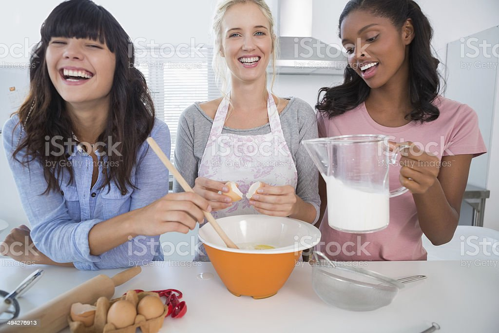Laughing friends making pastry together stock photo