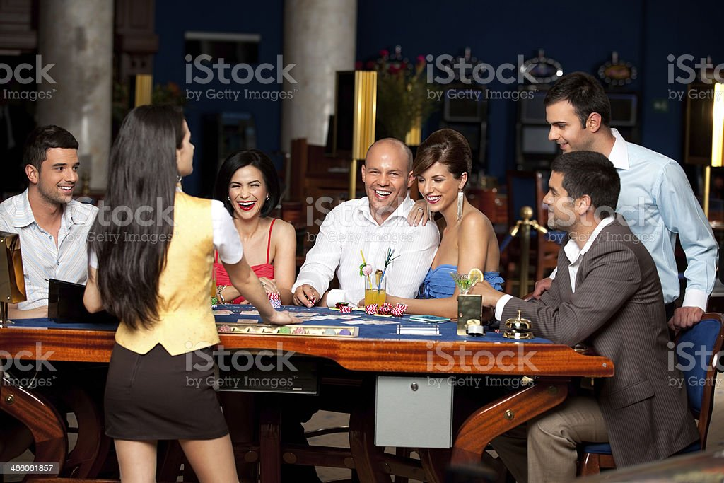 laughing friends playing cards in a casino stock photo