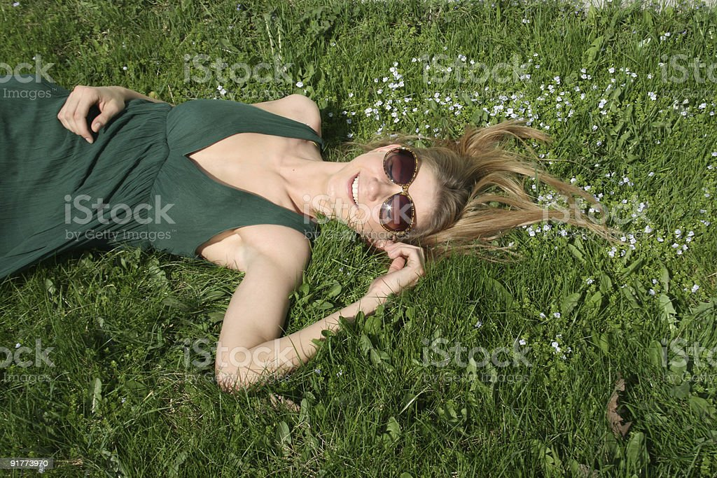 Laughing girl lying on grass royalty-free stock photo