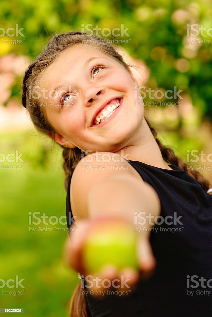 Laughing girl stretches an apple royalty-free stock photo