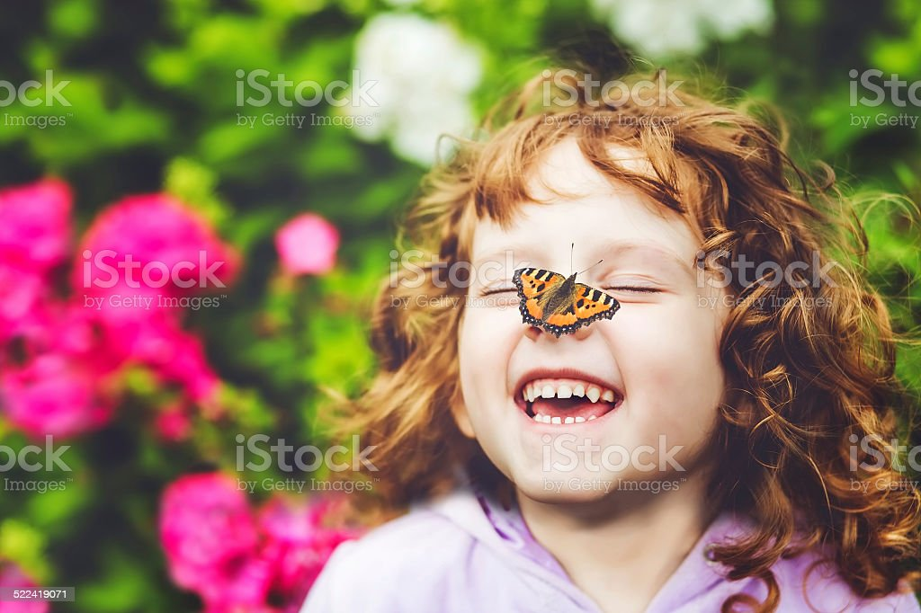 Laughing girl with a butterfly on his nose stock photo