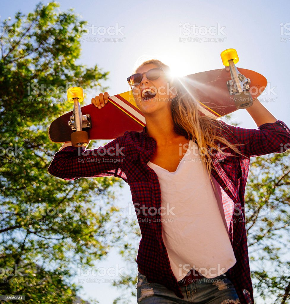 Laughing girl with skateboard stock photo