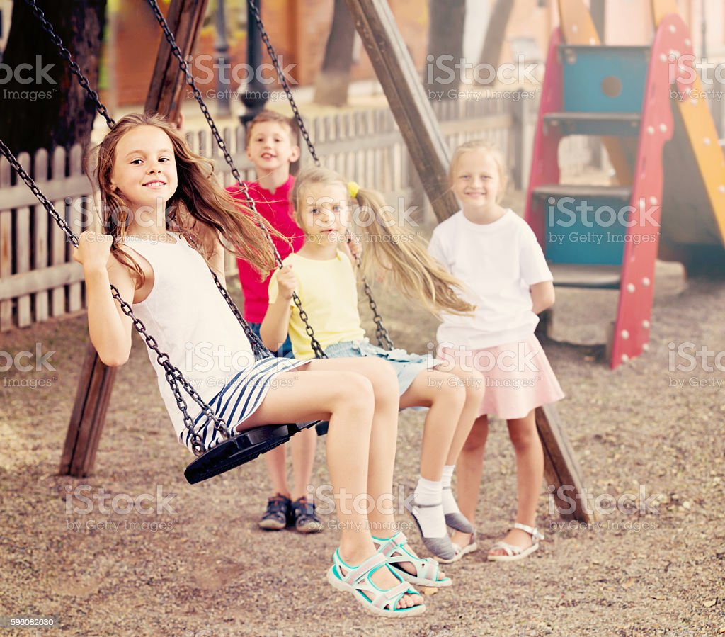 Laughing girls and boys swinging on playground stock photo