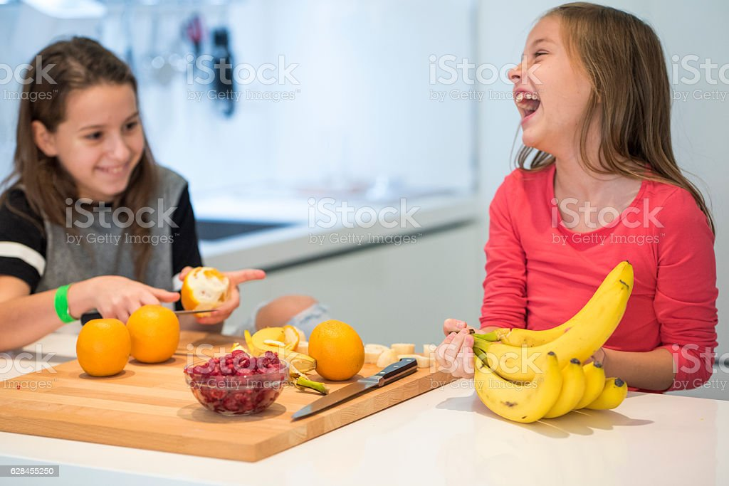 Laughing girls in the kitchen stock photo