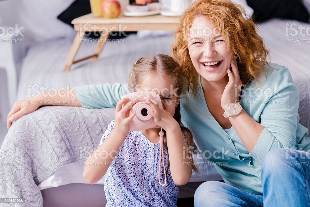 Laughing granddaughter taking photos with her grandmother stock photo