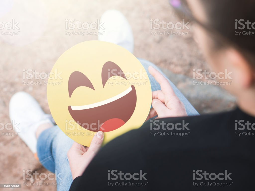 Laughing happy emoticon in hand. Woman holding a cheerful and joyful printed paper smiley face. Happy communication   and smiley icon on cardboard. Happiness, joy and expression concept. stock photo