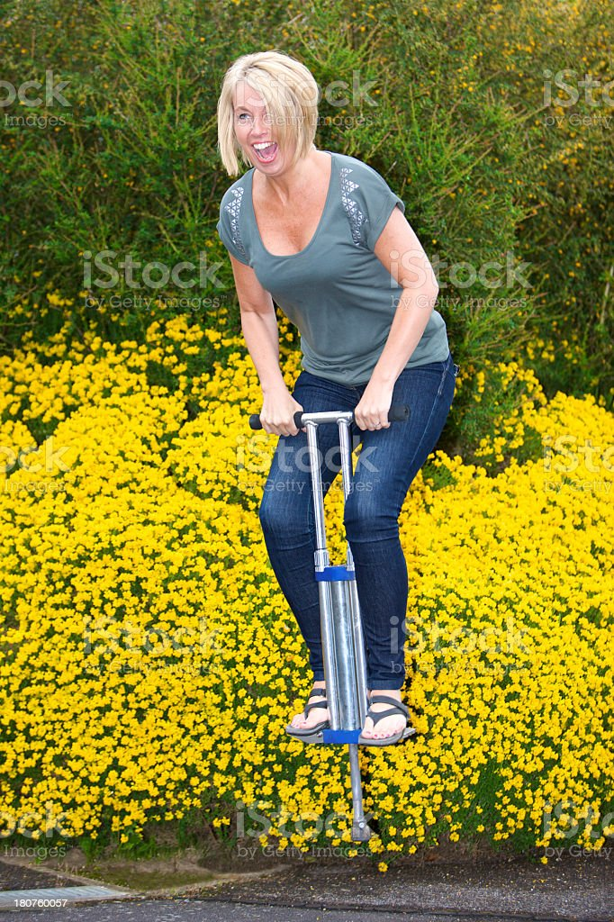 Laughing happy woman jumping about outdoors on a Pogo Stick stock photo