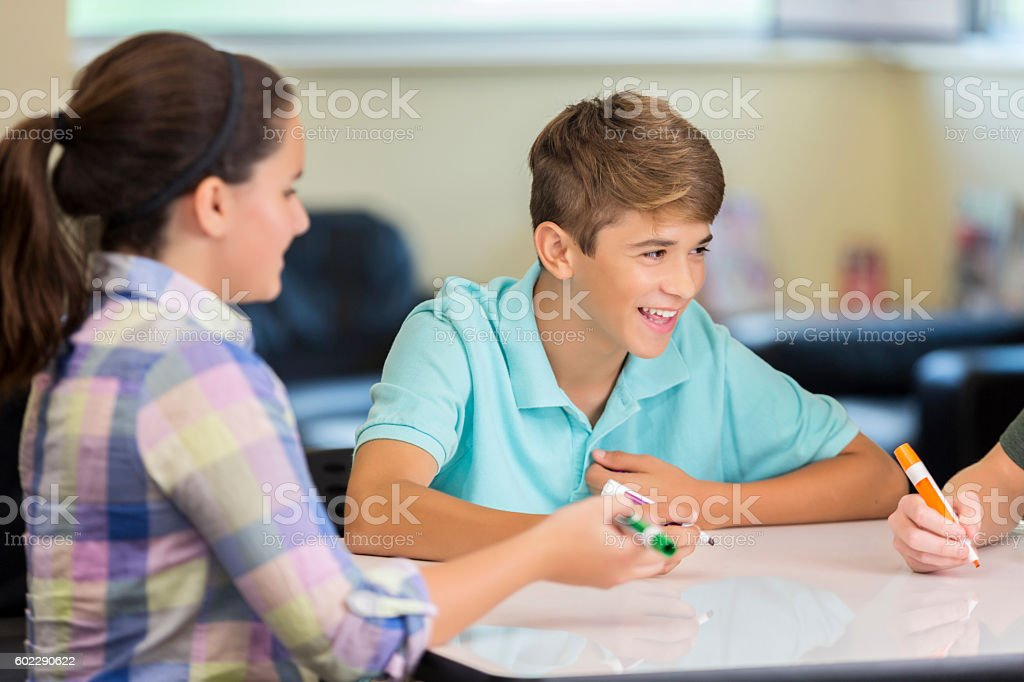 Laughing high school students brainstorming at makerspace animation station stock photo