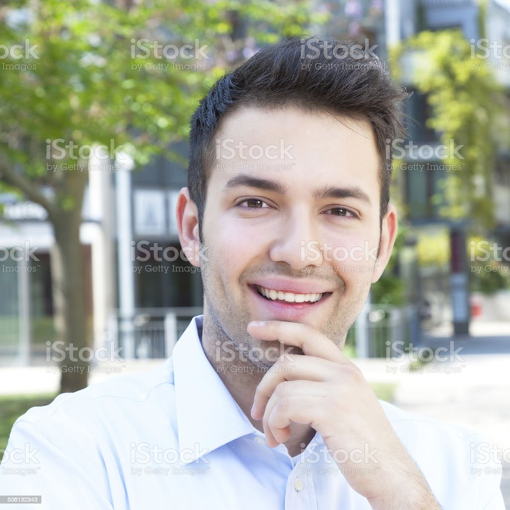 Laughing hispanic guy in a blue shirt stock photo