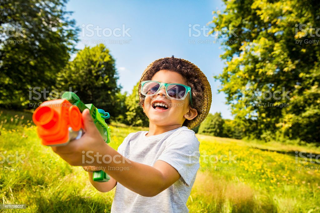 Laughing kid playing with squirt gun in park stock photo