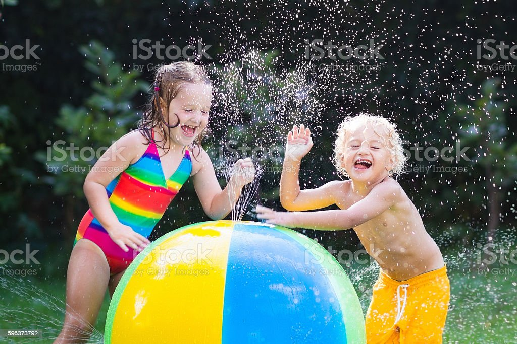 Laughing kids playing with water ball toy stock photo