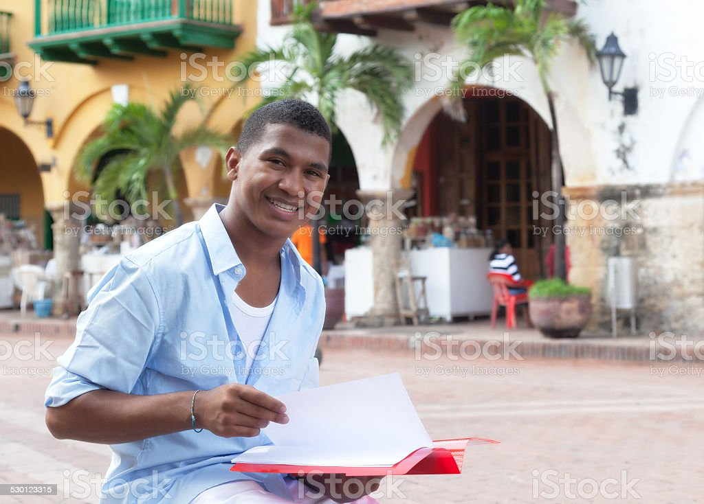 Laughing latin student in a colonial town with paperwork stock photo