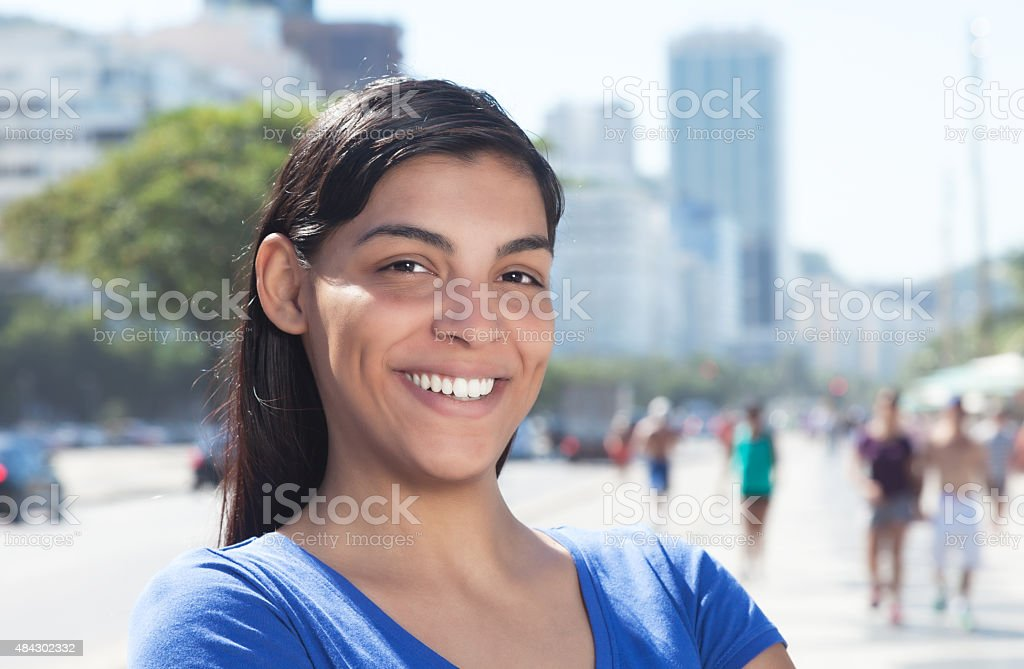 Laughing latin woman with long dark hair in the city stock photo