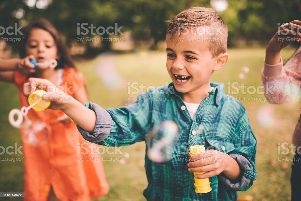 Laughing little boy playing with bubbles in the park stock photo
