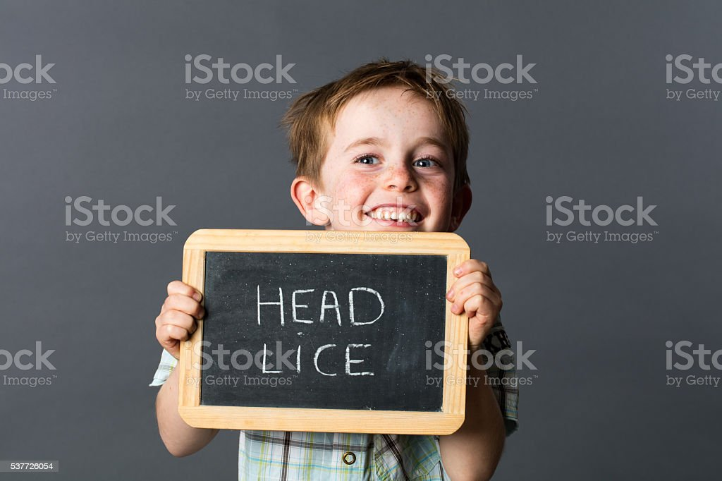 laughing little child warning about head lice to fight against stock photo