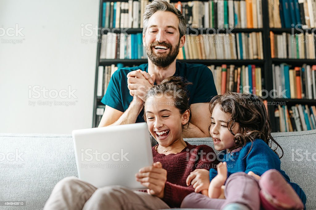 laughing little family on sofa looking tv at tablet computer stock photo