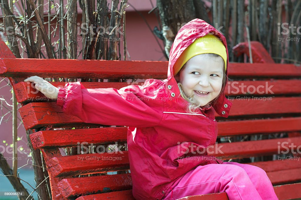 Laughing little girl leaning forward and sitting on red bench stock photo