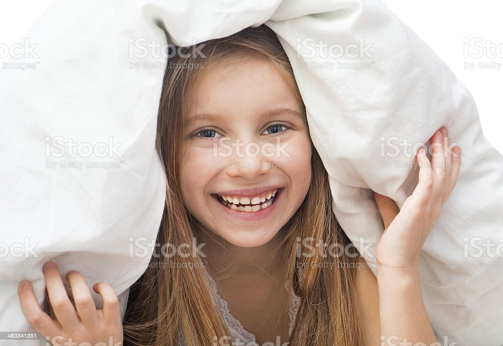 Laughing little girl under a blanket stock photo