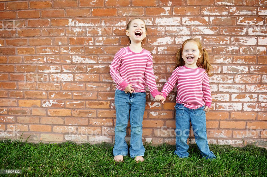 Laughing Little Sisters Holding Hands by Brick Wall royalty-free stock photo