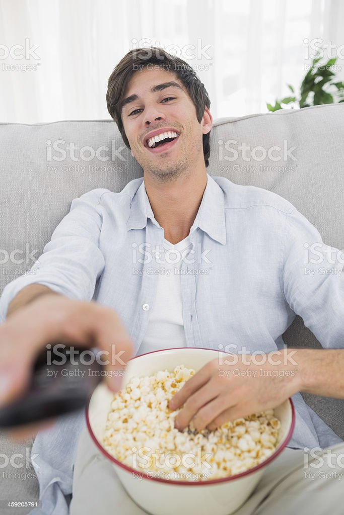Laughing man eating popcorn and holding remote control royalty-free stock photo