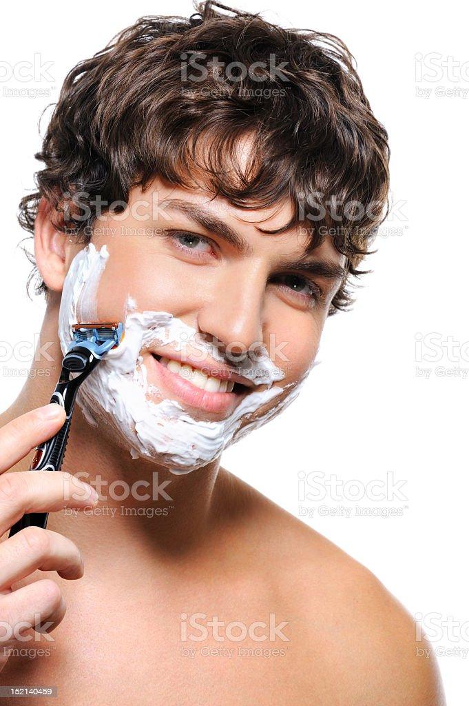 Laughing man enjoying himself while shaving stock photo