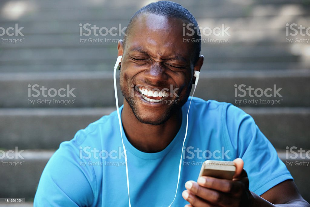 Laughing man holding cell phone listening with earphones stock photo