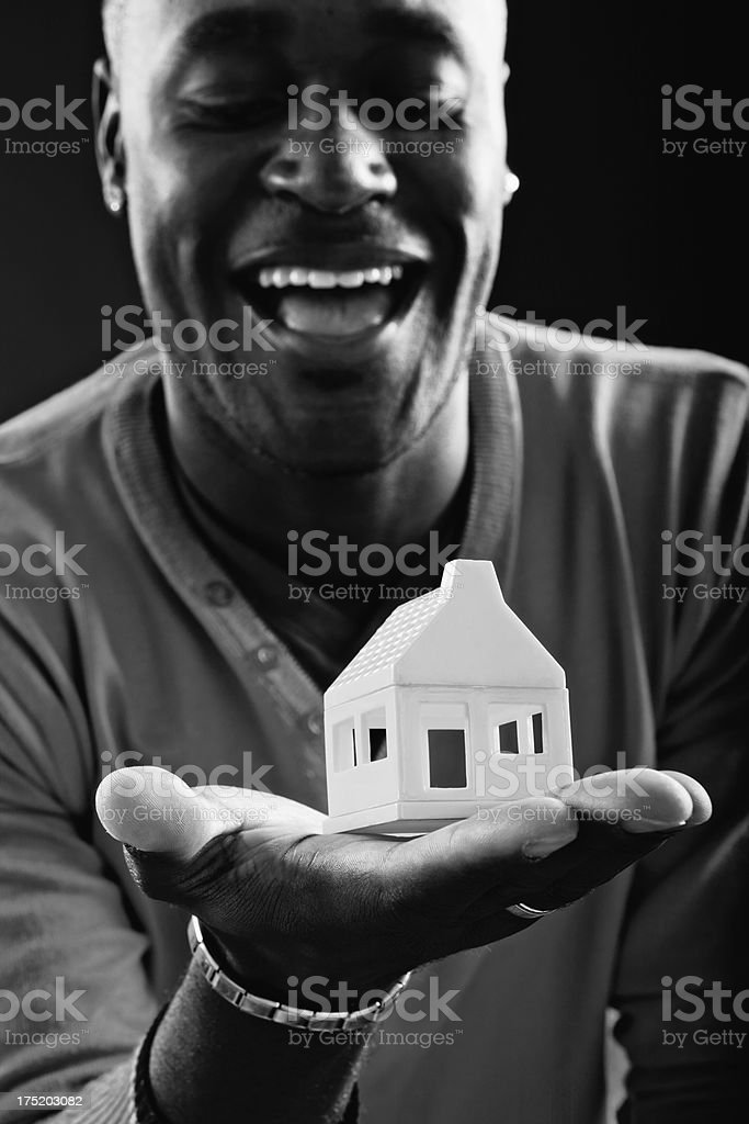 Laughing man looks down at toy house he holds stock photo