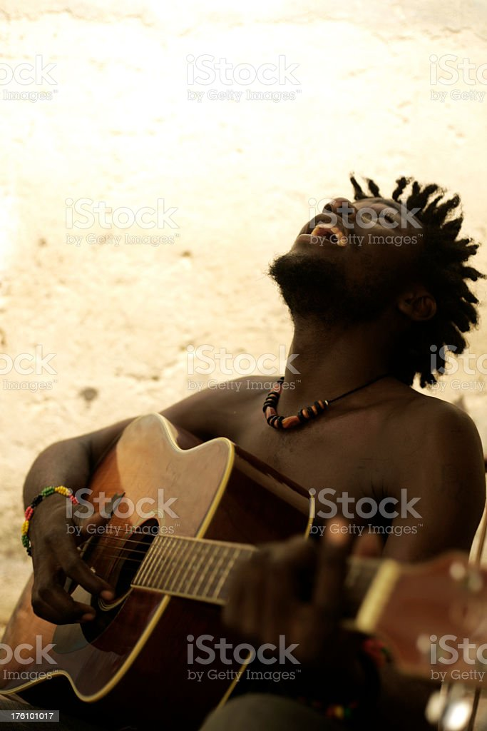 Laughing man playing the guitar, creating African music stock photo