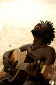 Laughing man playing the guitar, creating African music