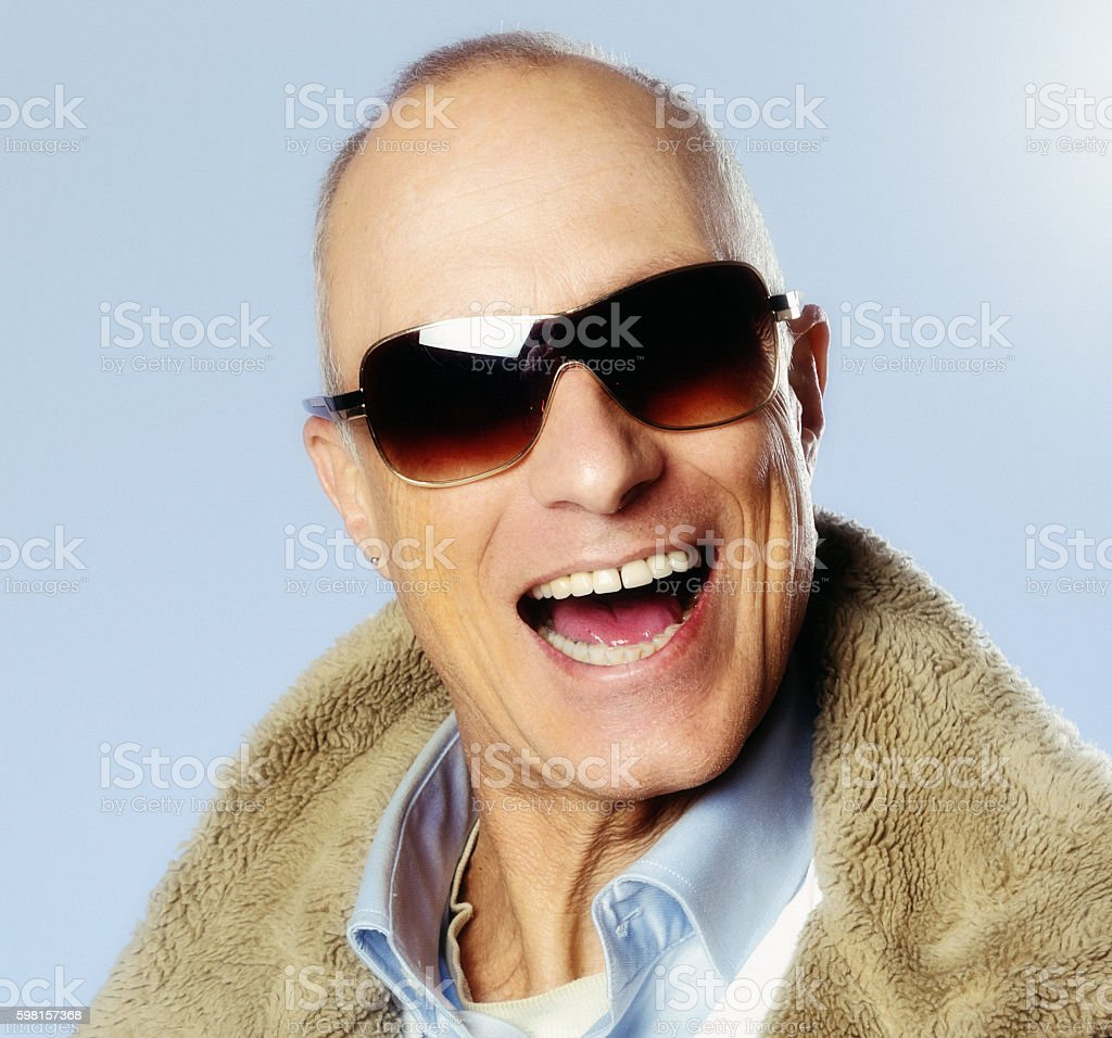 Laughing mature man in sheepskin jacket and sunglasses stock photo