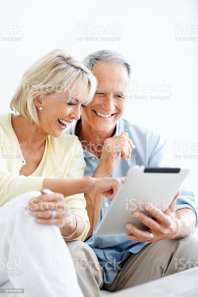 Laughing mature woman with a man pointing at touchpad screen royalty-free stock photo